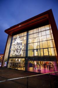 Через открытые витражи фасада хорошо просматриваются крупные формы дизайна интерьера торгово-развлекательного центра.